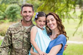 foto of veterans  - Handsome soldier reunited with family on a sunny day - JPG