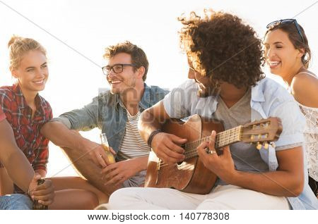 Happy friends having fun together while guy playing guitar. Group of young women and men enjoying th