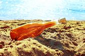 Orange bottle on yellow sand near blue water