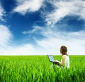 Young woman with laptop sitting on a green meadow and looking to a blue cloudy sky