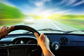 picture of driving  - Hands on steering wheel of a car driving on an asphalt blurred road - JPG