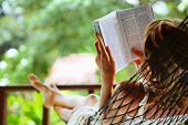 image of reading book  - Young woman reading a book lying in a hammock - JPG