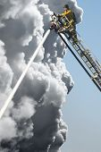 A Fire Man on a lift up high hosing a fire below him