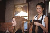 Female hairdresser straightening the hair of a client at a salon poster