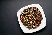 Red, Green, White Pepper, Pimento And Schinus In A Dish