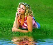 Cute Girl Lying Near The Rivershore poster