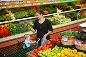 stock photo of fruits vegetables  - Woman with baby shopping in grocery store - JPG