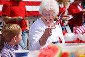 Elderly woman at family barbeque waving American flag