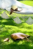 Straw hat with brown ribbon laying on summer hammock