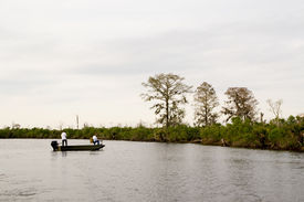 image of flatboat  - two fishermen in a small flatboat try their luck fishing in the North Pass to Lake Maurepas in the Manchac Swamp just north of New Orleans - JPG