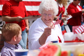 picture of waving american flag  - Elderly woman at family barbeque waving American flag - JPG