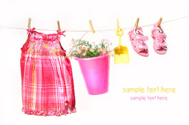 stock photo of wet pants  - Little girl clothes and toys on a clothesline against white background - JPG