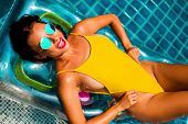 Amazing Beautiful Girl In A Yellow Bikini Air Mattress Swims In The Pool Of A Luxury Hotel, Summer V poster