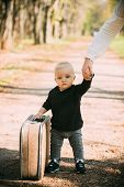 Travelling Child Carry Suitcase On Natural Landscape. Travelling Baby Boy Travel With Vintage Bag Wi poster