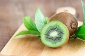 Fresh And Juicy Kiwi Fruit And A Half On Cutting Board. Ripe Kiwi Fruits On Wood Table In Side View  poster