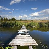 stock photo of cloud forest  - wooden bridge over river in steppe in nice day - JPG