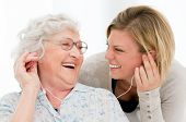 stock photo of granddaughter  - Excited grandmother listening music together with her granddaughter at home - JPG
