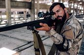 Постер, плакат: Concentrated And Professional Shooter Is Taking Aim He Is Looking Through Special Lens The Rifle I