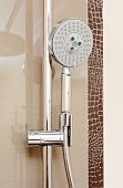stock photo of shower-cubicle  - Metal shower tap in modern bathroom with brown ceramics tile - JPG