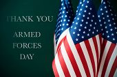 some american flags and the text thank you and armed forces day against a dark green background poster