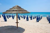 Straw Umbrella With Background Blue Sea, Sky And Sand Beach. Nobody, Outdoor. Italy, Puglia poster