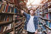 Young Man Stands In A Public Library And Shows A Finger Down. Dislike Library And Books. Student In  poster