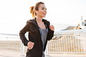 Attractive young sports woman running outdoors on the street listening music with earphones. poster