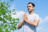 Serene Young Indian Man Meditating Outdoors With His Eyes Closed And Blue Sky In Background. Meditat poster