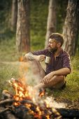 Man Traveler Drink Tea At Campfire Flame. Camping, Hiking, Lifestyle. Summer Vacation Concept. Hipst poster