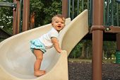 stock photo of slip hazard  - Baby girl standing on the edge of a slide on a playground - JPG