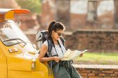 Young Asian Female Traveler With Backpack Traveling Standing On Taxi Or Tuk Tuk And See Map Travel W poster