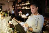 Young pretty mixed race waitress standing at bar counter and processing order of customer in POS sys poster
