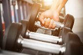 Close Up Of Man Holding Rows Of Dumbbells In The Gym.gym Equipment And Sport Concept. poster