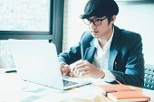 Handsome Young Businessman Sitting In A Modern Corporate Environment, And Working With Laptop Comput poster