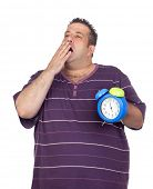 Fat man with a blue alarm yawning clock isolated on white background