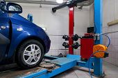 Blue Car Front Wheel View Stands On The Stand Wheel Alignment Convergence Of The Car During Regular  poster