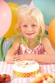 Young girl with birthday cake at party