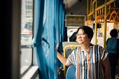 Asian Woman Travel By Passenger Bus In City poster