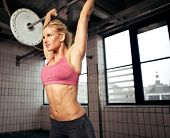 foto of bodybuilder  - Woman doing shoulder press exercise with a weight bar inside a gym - JPG