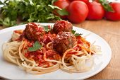 stock photo of veal meat  - plate of spaghetti with meatballs in tomato marinara sauce and ingredients on a wooden table - JPG