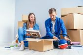 Young Couple Unpacking Things After Moving Into New House poster