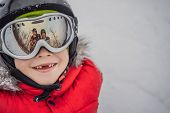 Mom And Dad Are Reflected In The Boy Ski Goggles. Mom And Dad Teach A Boy To Ski Or Snowboard poster