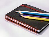 Black Note Book With Colored Pencils