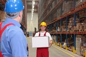Worker Bringining Box In Warehouse