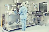 Pharmaceutics. Pharmaceutical worker operates blister packaging machine poster