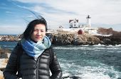 A Chinese Woman Traveling In America With The Cape Neddick Nubble Lighthouse In The Back Ground In C poster