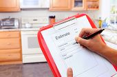 Closeup of a contractors clipboard as he writes up an estimate for a kitchen remodel. Shallow depth
