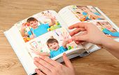 Photos in hands and photo album on wooden table
