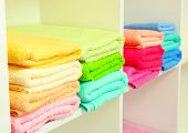 toallas de colores en estantes en el baño