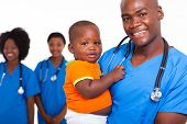 portrait of good looking african american male pediatric doctor with little boy and female nurses on